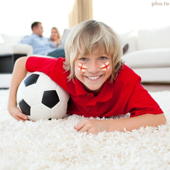 Young football fan with England face paint watches FIFA World Cup.