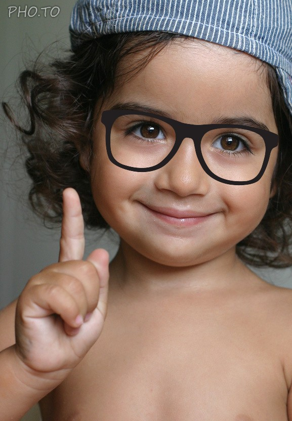 Hipster glasses are put on a face photo of a cute little child.