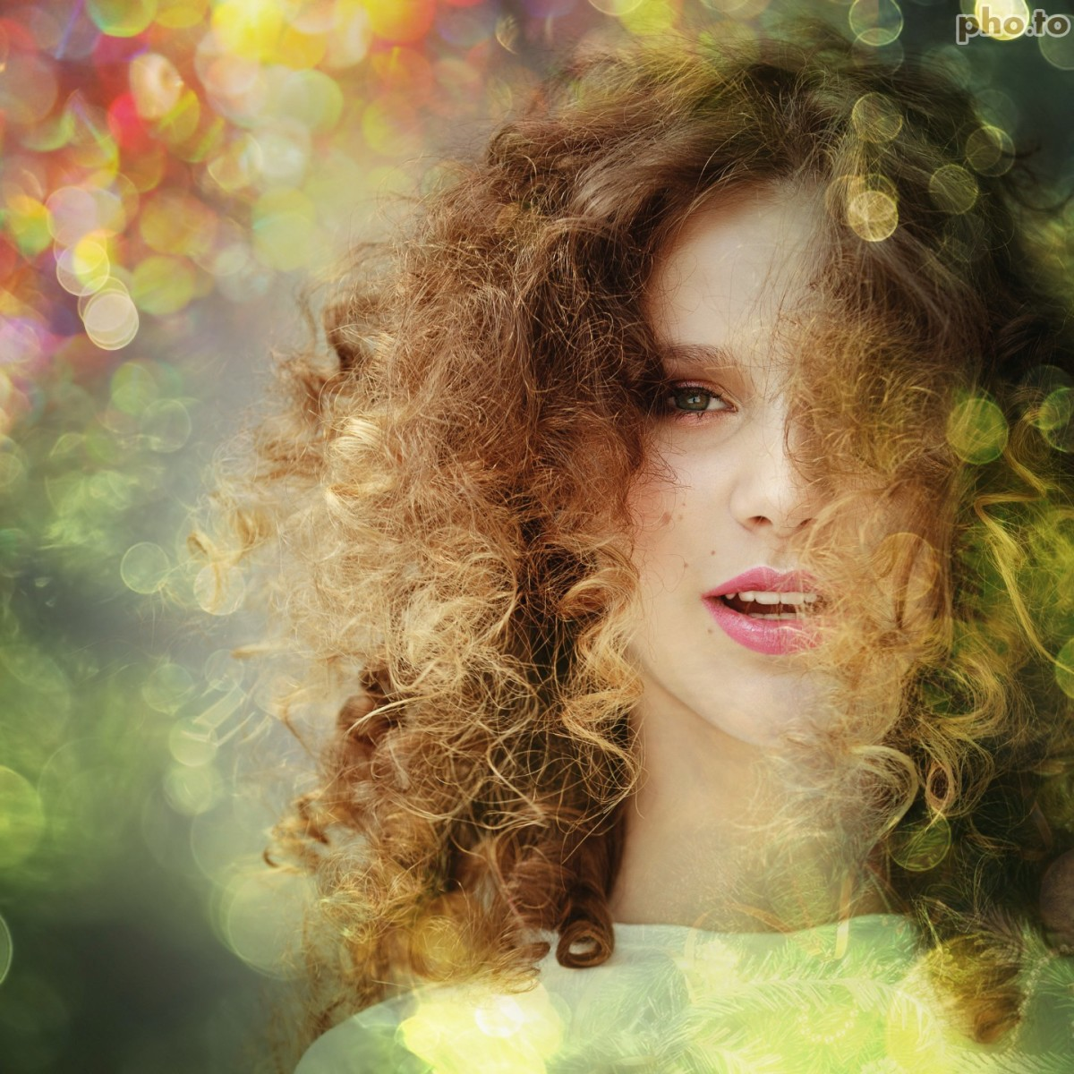 Blurred Christmas lights are added to a photo portrait of a curly girl