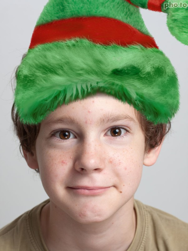 Boy elf in a photo looks like a Christmas elf in his virtual Christmas elf hat.