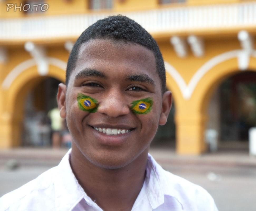 Brazil flag in green, yellow and blue colors painted on man's cheeks.