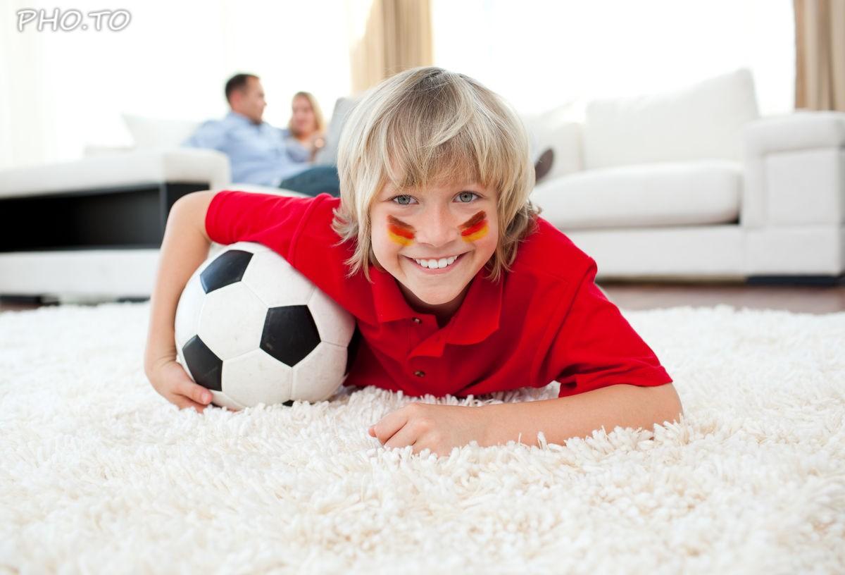 Junger Fussballfan hat Deutschland Flagge im Gesicht.