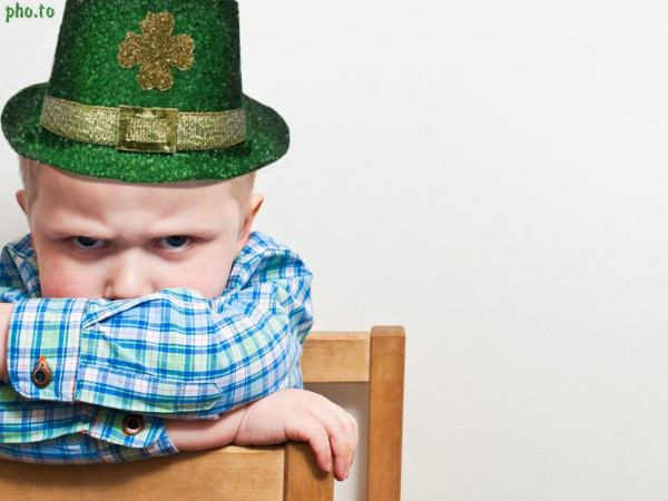 A boy in a St Patrick's hat with an irish decoration clover on it.