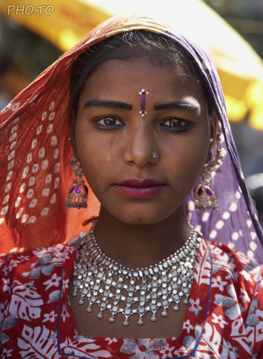 Tears are added to a face photo of a young Indian in traditional clothes